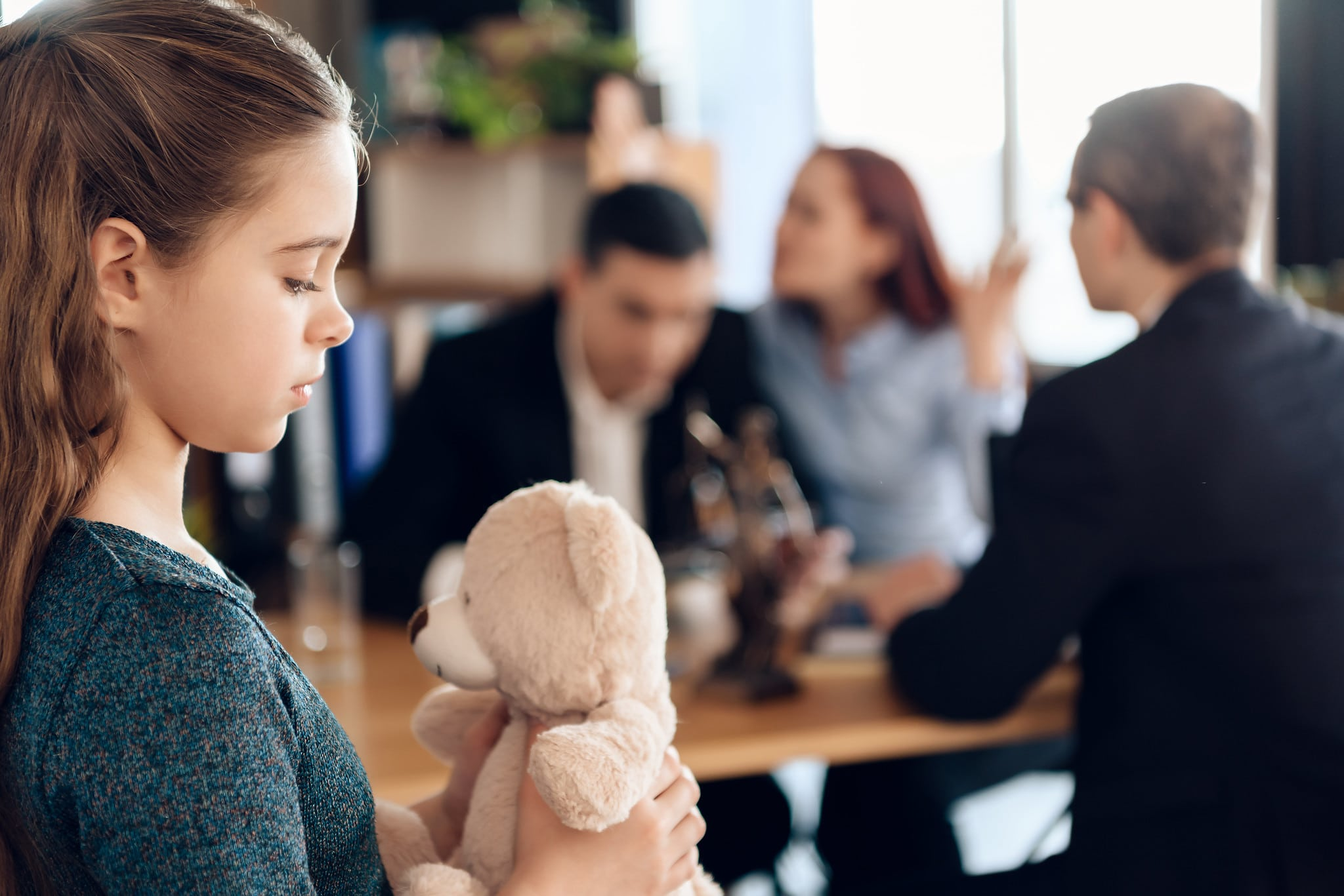 girl holding a teddy bear while her parents argue in the background