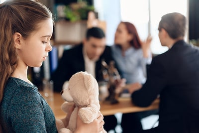 Young girl holding her stuffed animal while her parents argue